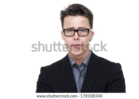 Handsome young businessman, professor or student in nerdy glasses with a serious expression and perplexed frown looking intently at the camera, head and shoulders isolated on white with copyspace - stock photo