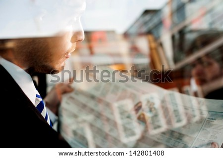 Handsome young businessman reading newspaper inside taxi cab. - stock photo