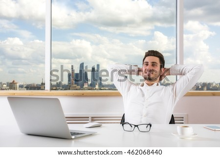 Handsome young businessman relaxing in modern bright office room with city view