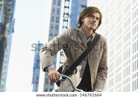 Handsome young businessman riding bicycle in downtown district - stock photo