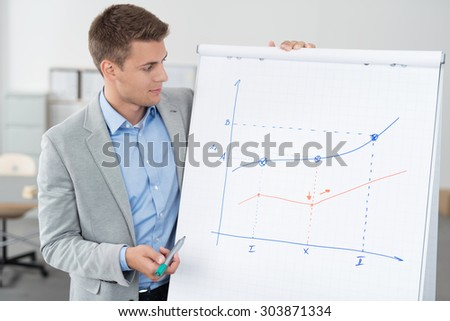 Handsome Young Businessman Showing his Conceptual Business Graph on a Poster Paper While Holding a Marker Pen. - stock photo