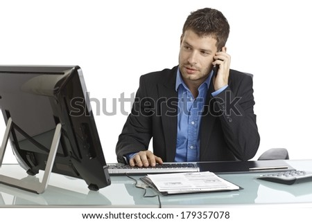 Handsome young businessman sitting at desk, using computer and mobilephone. - stock photo