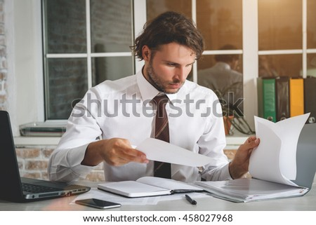 Handsome Young Businessman Sitting At His Workplace Holding A Paper And Looking At Folder With Documents. Business Theme