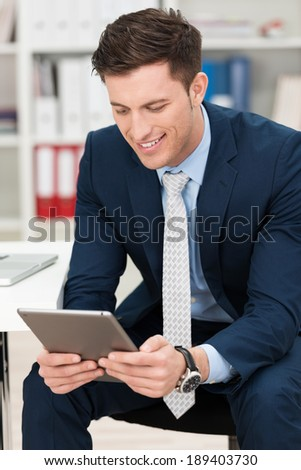 Handsome young businessman sitting in his office smiling as he reads information on his his tablet computer screen - stock photo