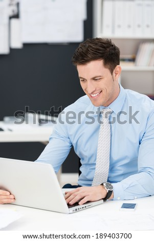 Handsome young businessman smiling as he works at his desk reading information on his laptop computer - stock photo