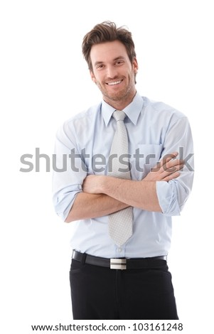 Handsome young businessman standing arms crossed, smiling confidently. - stock photo