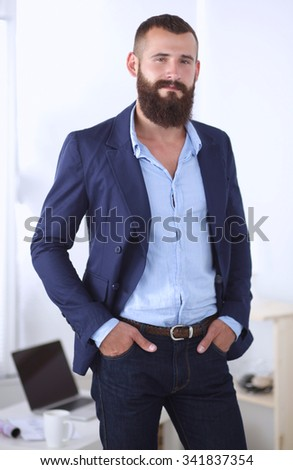 Handsome young businessman standing in office