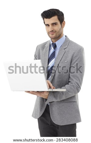 Handsome young businessman standing, working on laptop computer, looking at camera, smiling. - stock photo