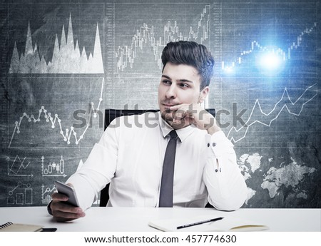 Handsome young businessman thinking about something sitting in front of black wall with sketch of graphs on it. Concept of thinking - stock photo