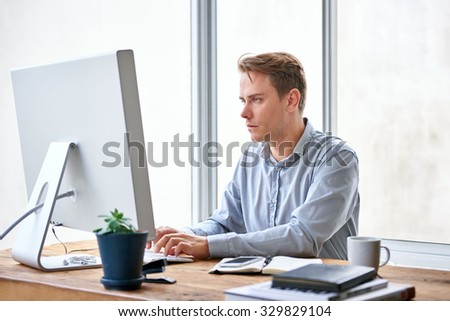 Handsome young businessman typing on his keyboard while sitting at his desk working  - stock photo