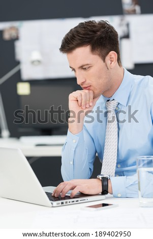 Handsome young businessman using a laptop sitting thinking at his desk as he reads information on the screen - stock photo