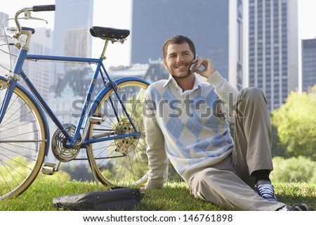 Handsome young businessman using cell phone by bicycle in park - stock photo