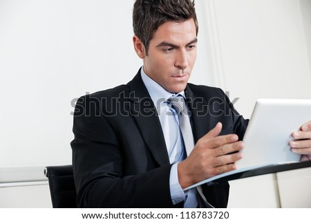 Handsome young businessman using digital tablet in office - stock photo