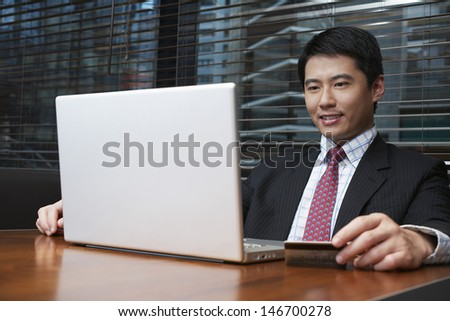 Handsome young businessman using laptop and credit card at restaurant table - stock photo