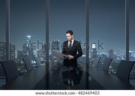 Handsome young businessman using laptop computer in conference room interior with table, chairs and night city view. 3D Rendering