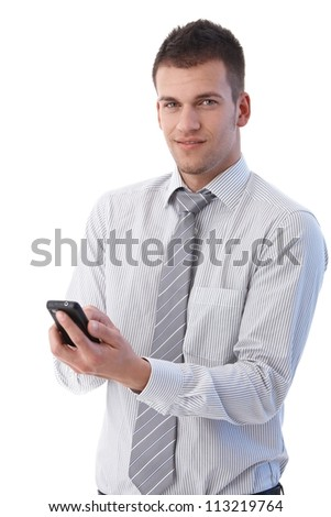 Handsome young businessman using mobile phone, writing text message, smiling. - stock photo