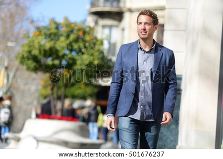 Handsome young businessman walking on city street in the morning going to work in office wear smart casual outfit of wool suit and blue jeans. Urban lifestyle of young professionals. Caucasian man.
