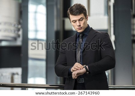 Handsome young businessman Watching on his watch in modern office. - stock photo