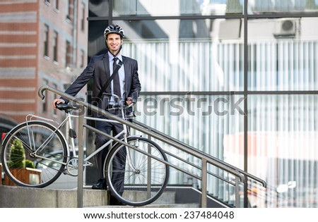 Handsome young businessman with a cycle helmet on head carrying bicycle down steps - stock photo