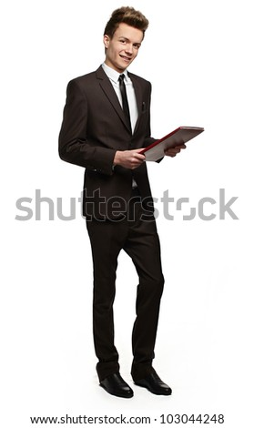 Handsome young businessman with a folder in his hands  with a slight smile on his face