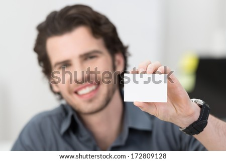 Handsome young businessman with a lovely friendly smile holding up his blank white card card to show his credentials and qualification - stock photo