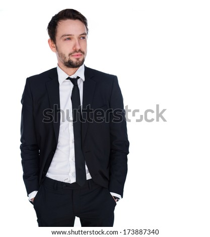 Handsome young businessman with a thoughtful expression standing with his hand in his pockets staring off into the distance in contemplation, isolated on white with copyspace - stock photo