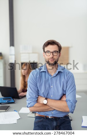 Handsome Young Businessman with Arms Closed Leaning Against the Table with his Female Co-worker Behind Him. - stock photo