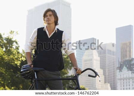 Handsome young businessman with bicycle standing in city park - stock photo