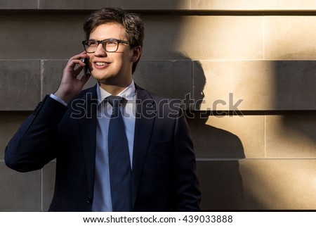 Handsome young businessman with glasses having mobile phone conversation outside on concrete tile background - stock photo