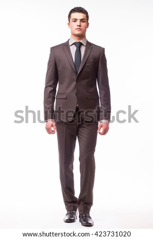 Handsome young businessman  with luck in suit standing against white background - stock photo