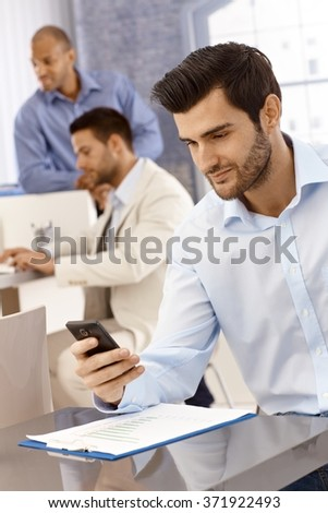 Handsome young businessman working in office, using mobilephone, texting.