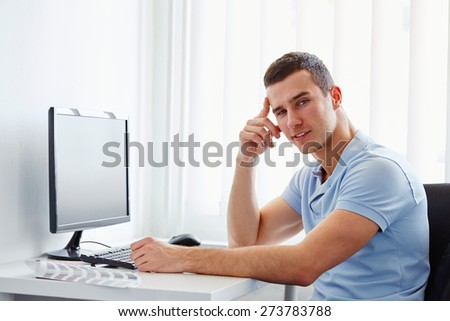 Handsome young businessman working in the office - stock photo