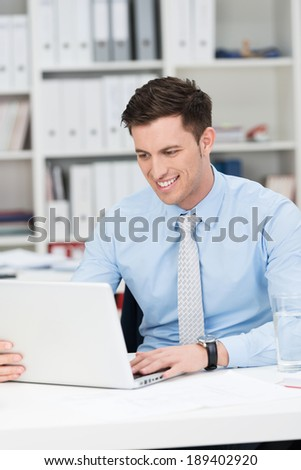 Handsome young businessman working in the office sitting at his desk smiling as he reads information on his laptop screen - stock photo