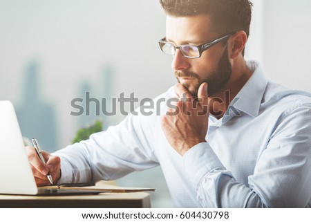 Handsome young businessman working on project at workplace. Work concept