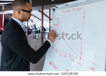 Handsome young businessman writing on a flipchart at the office - stock photo