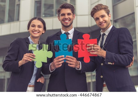 Handsome young businessmen and lady in classic suits are holding colorful pieces of puzzle, looking at camera and smiling, standing outside the office building