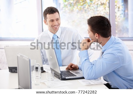 Handsome young businessmen chatting in meeting room, smiling.? - stock photo