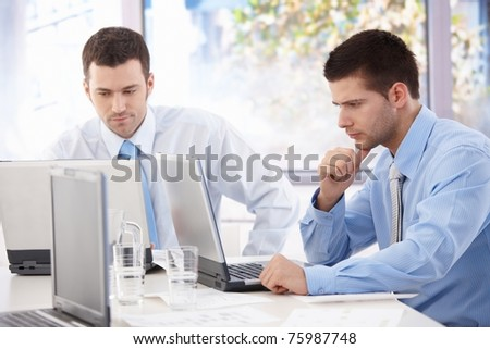 Handsome young businessmen working on laptop in bright office.?