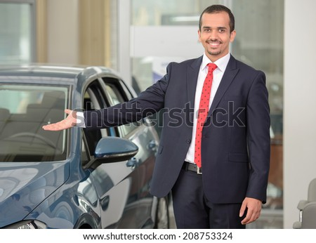 Handsome young car salesman standing at the dealership and pointing car
