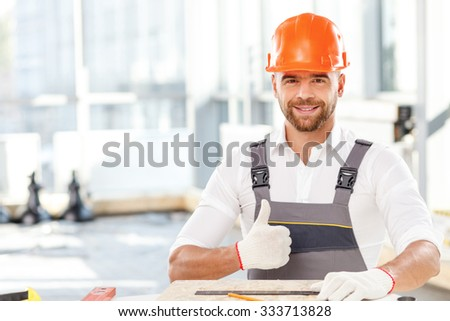 Handsome young carpenter is making measurements of wood board. He is sitting at table and holding a ruler. The man is looking forward and smiling. He is giving thumb up - stock photo