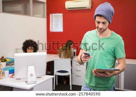 Handsome young casual businessman text messaging in office - stock photo