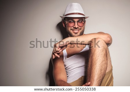 Handsome young casual man sitting and leaning on a white wall, resting his arm on his knee while smiling at the camera. - stock photo