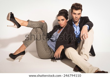 Handsome young casual man sitting on the floor while his girlfriend is leaning on him. - stock photo