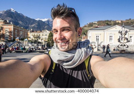 Handsome young caucasian guy is taking a selfie outdoor - people, technology and lifestyle concept - stock photo