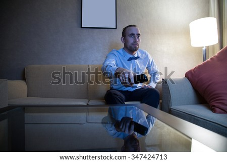 Handsome young caucasian man in a blue shirt and bow tie watching TV