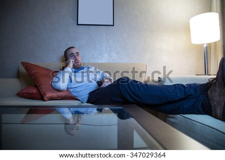 Handsome young caucasian man in a blue shirt and bow tie watching TV and calling by phone