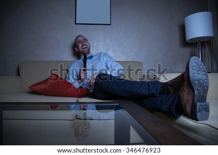 Handsome young caucasian man in a blue shirt and bow tie watching TV laughing