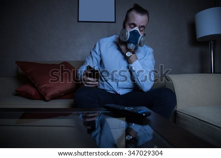 Handsome young caucasian man in a blue shirt and respirator watching TV coughing