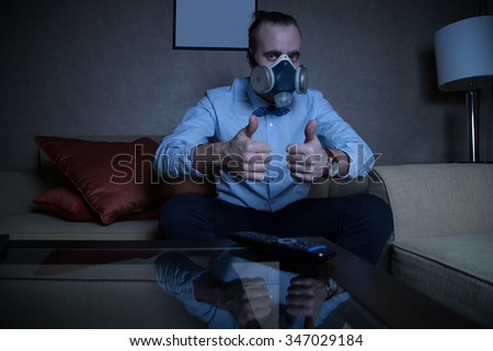Handsome young caucasian man in a blue shirt and respirator watching TV thumbs up - stock photo