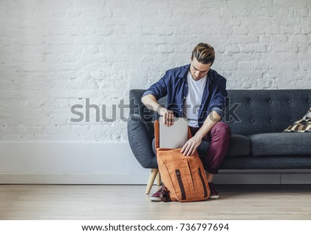Handsome young Caucasian  man packing laptop in backpack.